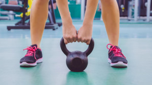 Woman ready to lift kettlebell in crossfit training